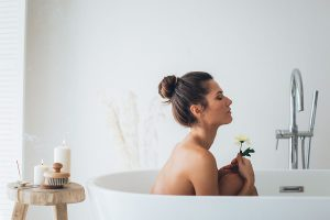 topless-woman-sitting-on-white-ceramic-bathtub-holding-flower